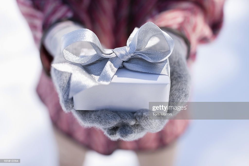 Close up of hands cupping Christmas gift with silver ribbon : Stock Photo