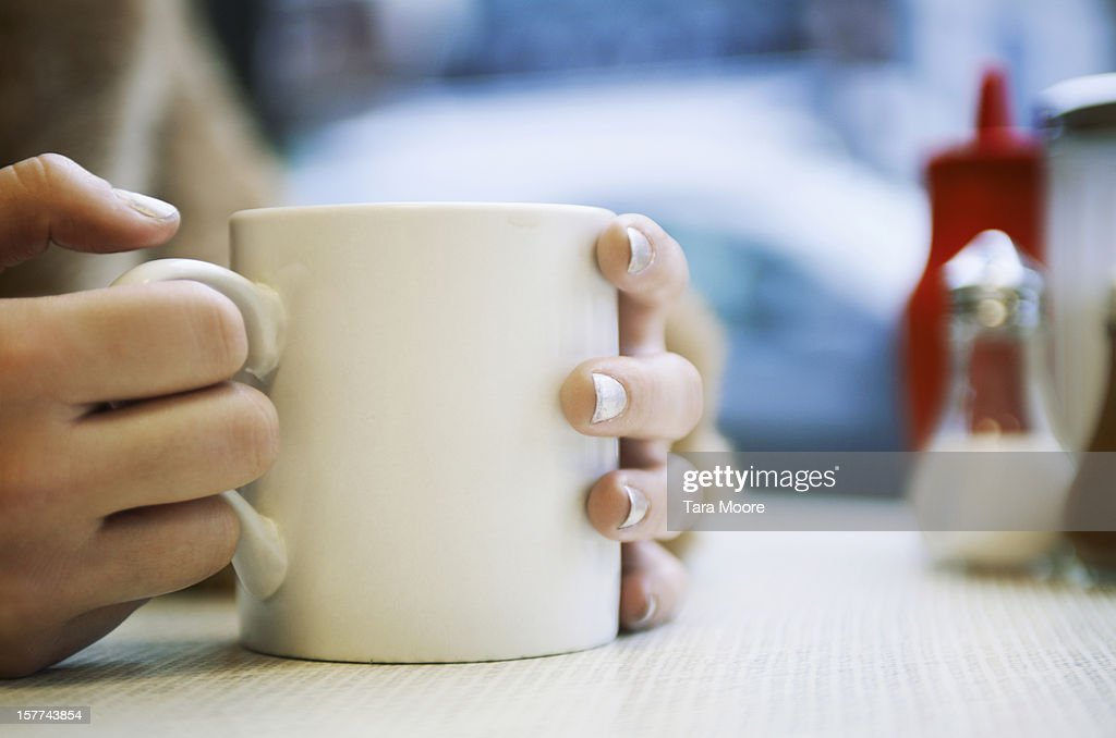 close up of hands holding cup of coffee in cafe : Stock-Foto
