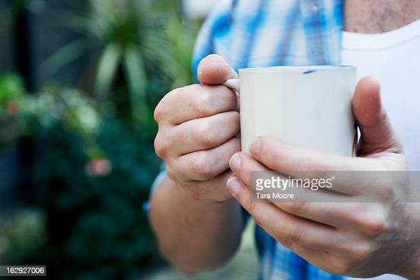 close up of hands holding cup of coffee