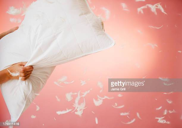 Close up of hands holding pillow with feathers flying around