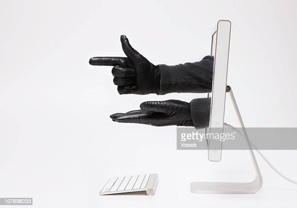 Close up of hands in black gloves emerging through monitor