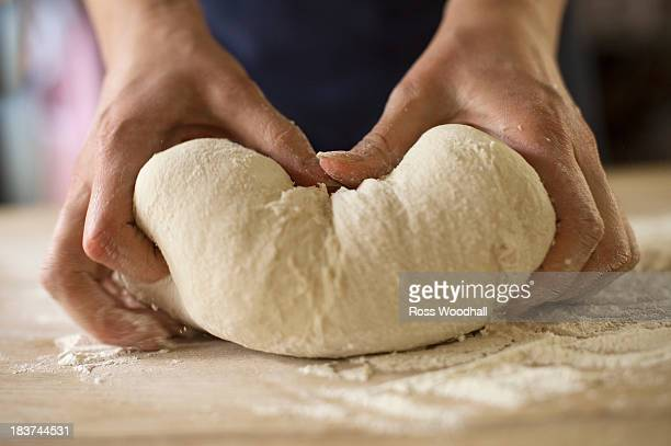 Close up of hands kneading bread dough