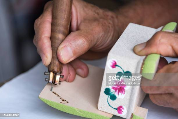 Close up of hands of an artisan pyro engraving a wooden artisanal box Tourism souvenirs