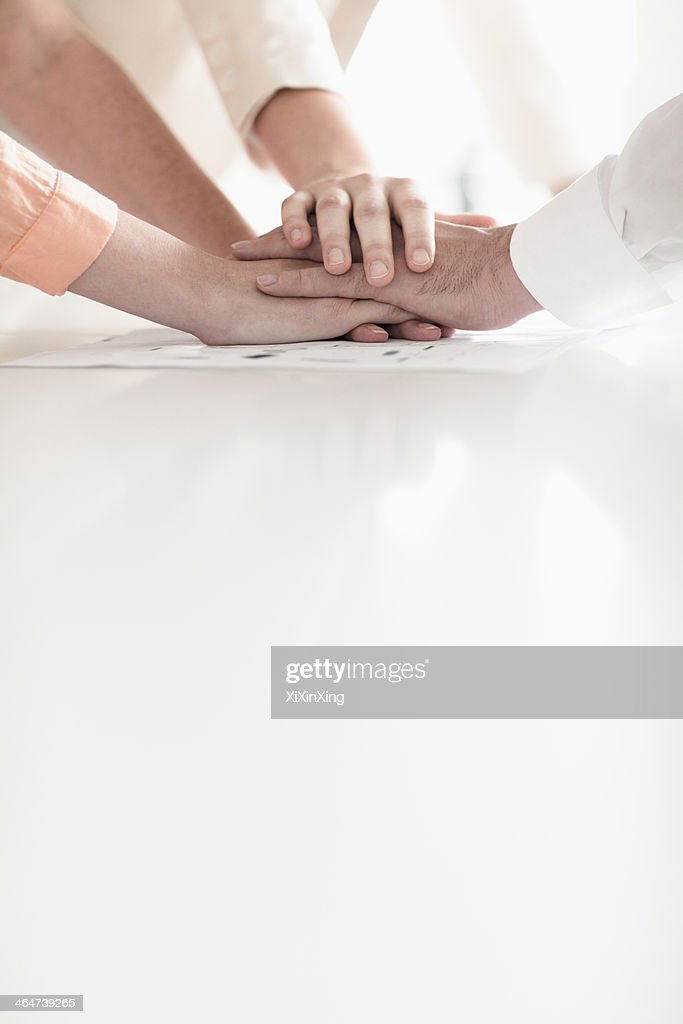 Close up of hands of business people on top of each other in partnership : Photo