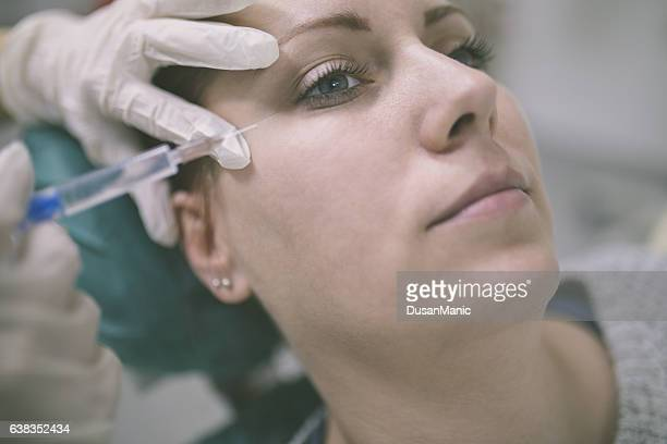 Close up of hands of cosmetologist making botox injection