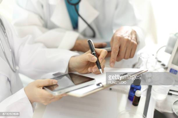 Close up of hands of doctor writing on a clipboard