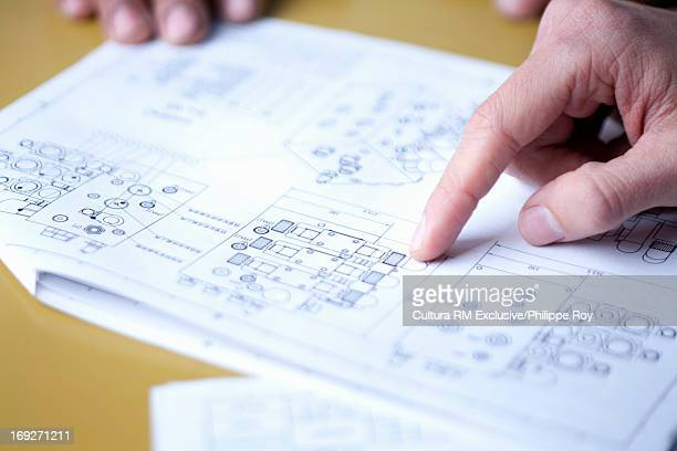 Close up of hands pointing to blueprints