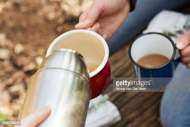 Close up of hands pouring drink from flask in cups, outdoors.