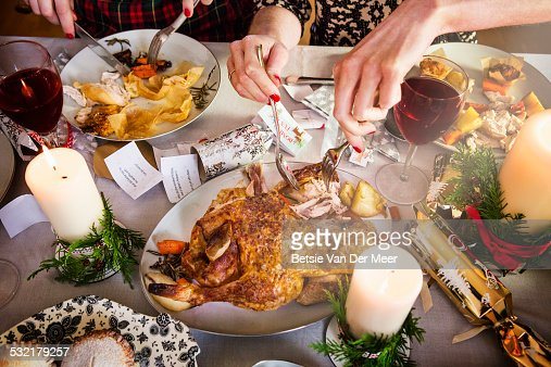 Close up of hands taking turkey and cutting food.