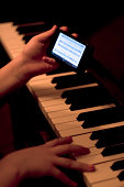 Close up of hands using smartphone whilst playing piano