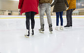 people, friendship, sport and leisure concept - close up of happy friends skating on ice rink