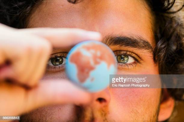 Close up of Hispanic man holding miniature globe