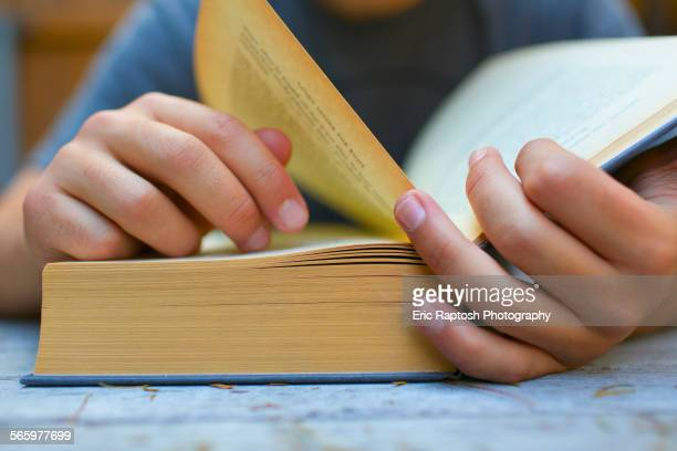 Close up of Hispanic man turning book pages