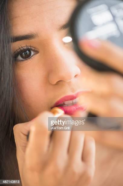 Close up of Hispanic woman applying lipstick in compact mirror