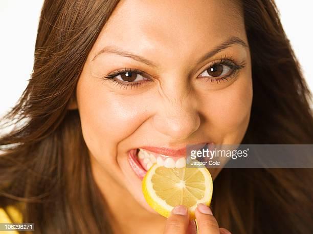 Close up of Hispanic woman biting lemon slice