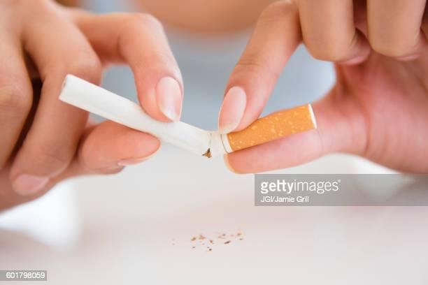 Close up of Hispanic woman breaking cigarette
