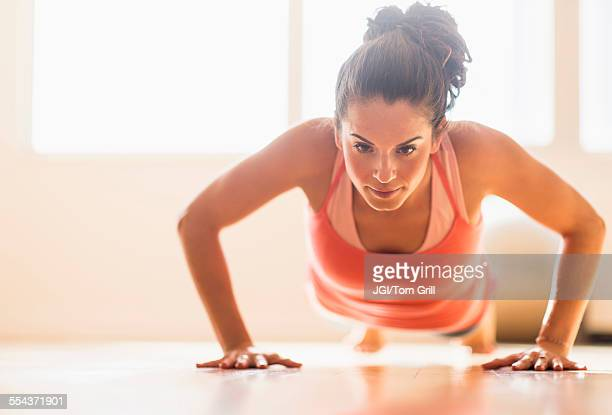 Close up of Hispanic woman doing push-ups in gym