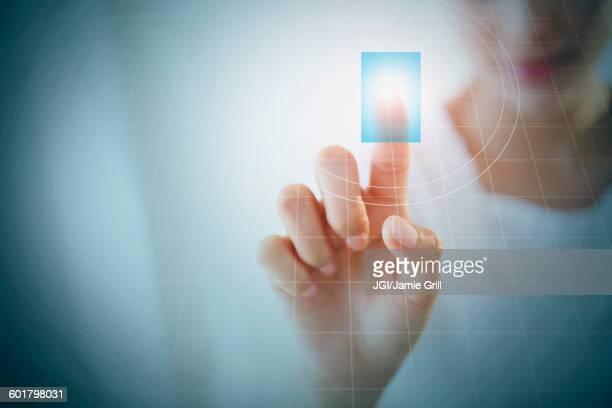 Close up of Hispanic woman touching digital screen