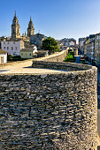 Close up view of historic Roman walls in downtown Lugo, Galicia, Spain. In the distance, the towers of St Mary's catholic cathedral.