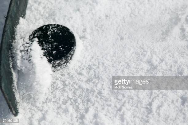 Close up of hockey stick and puck on ice