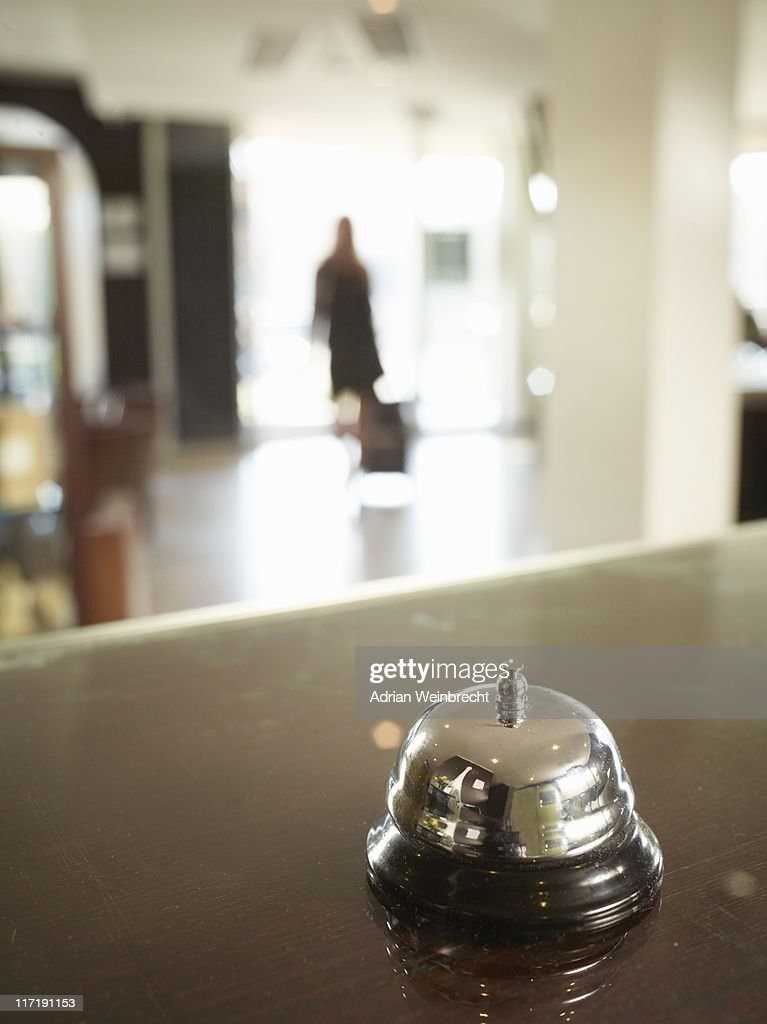 Close up of hotel porters bell with woman approaching : Stock Photo