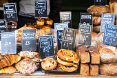 Close up color image depicting a large selection of artisan gourmet breads and pastries displayed on a bakery stall at Borough Market, London, UK, one of the most popular and oldest food markets in th