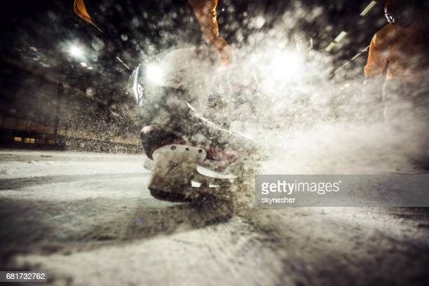 Close up of ice hockey player in motion on ice hockey rink.