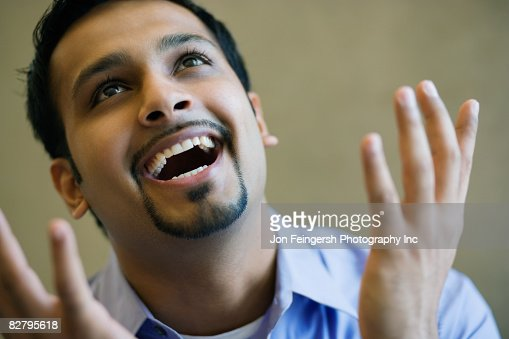 Close up of Indian businessman smiling and gesturing : Stock Photo