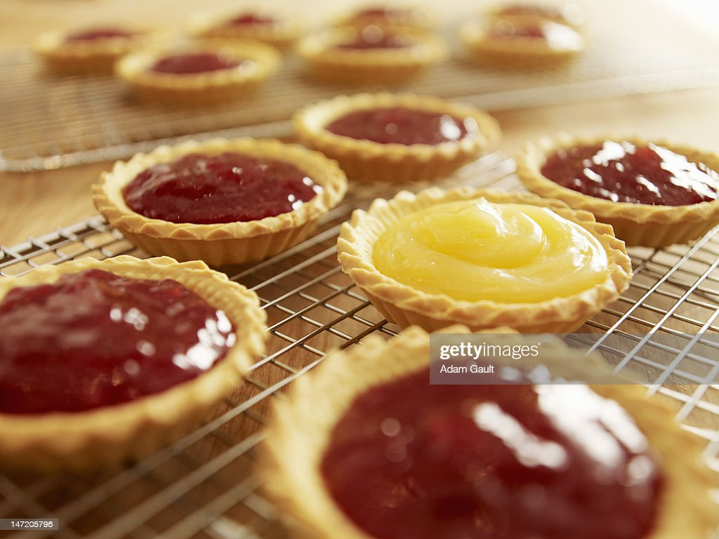 Close up of jam tarts cooling on wire racks : Stock Photo