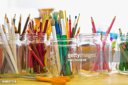 Close up of jars of colored pencils and paintbrushes