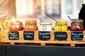 Close up color image depicting glass jars of sauce - tomato sauce, mustard, barbecue sauce, mayonnaise, chilli sauce - in a row at an outdoor burger stall at a food market. Focus is on the jars in the