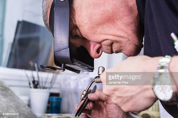 Close up of jewellery craftsman using miniature blowtorch