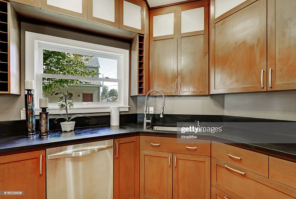 Close up of kitchen cabinets, black counter top ,small window : Stock-Foto