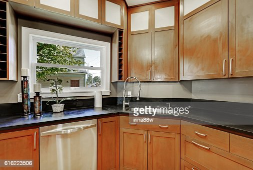 Close up of kitchen cabinets, black counter top ,small window : ストックフォト