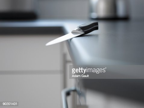 Kitchen Counter Close Up close up of kitchen knife about to fall off counter stock photo