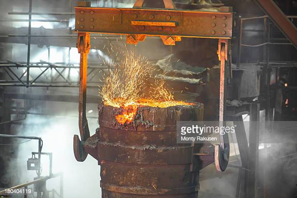 Close up of ladle full of molten metal in industrial foundry