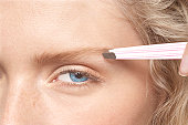 close up of lady plucking her eyebrow with tweezer