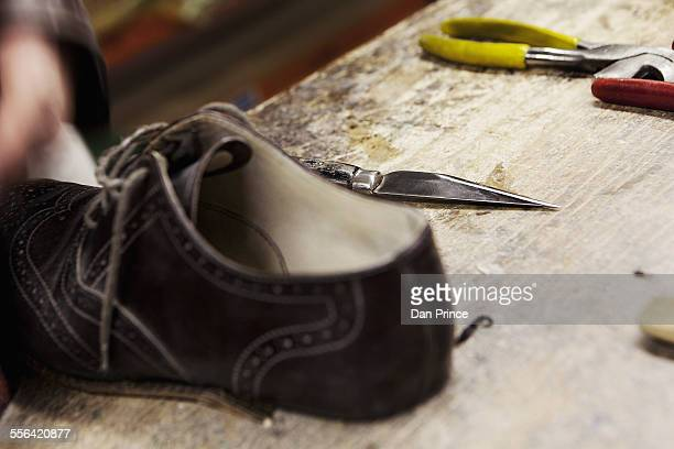 Close up of leather brogue and hand tools in shoe makers workshop
