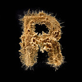 Close up of letter r made of sand on black background