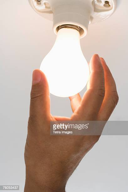 Close up of lightbulb being screwed in