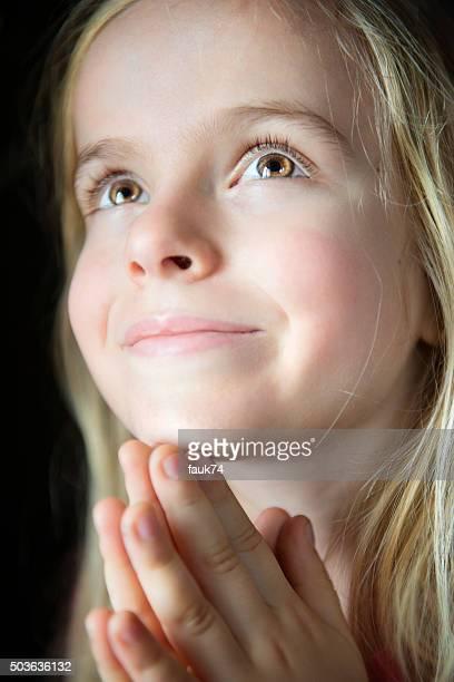 Primo piano di una bambina pregare.