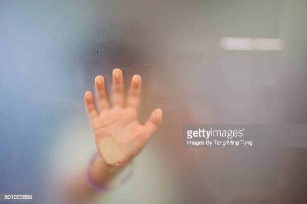 Close up of little girl's hand against the glass