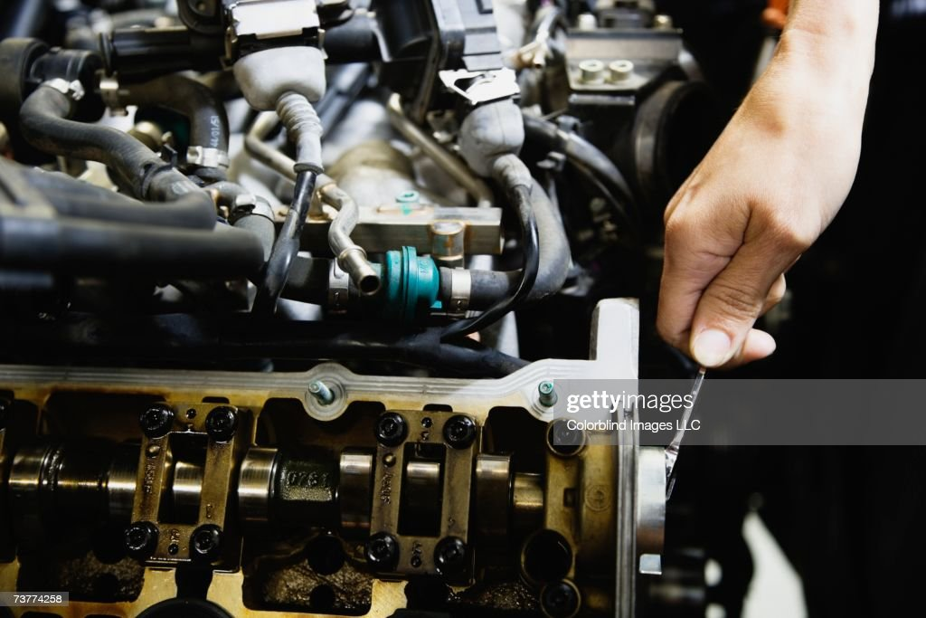 Close up of male auto mechanic working on engine