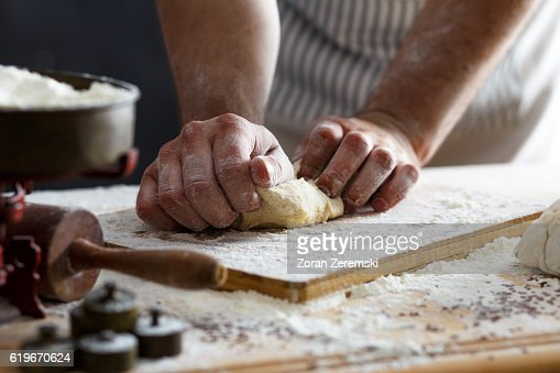 Close up of male baker hands kneading dough : Stock Photo