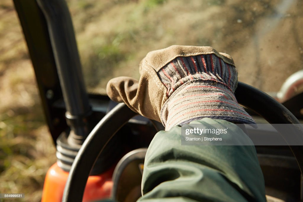 Close up of male hand driving tractor dairy farm field