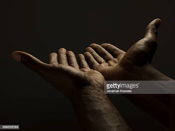 Close up of male hands reaching out, dark skin