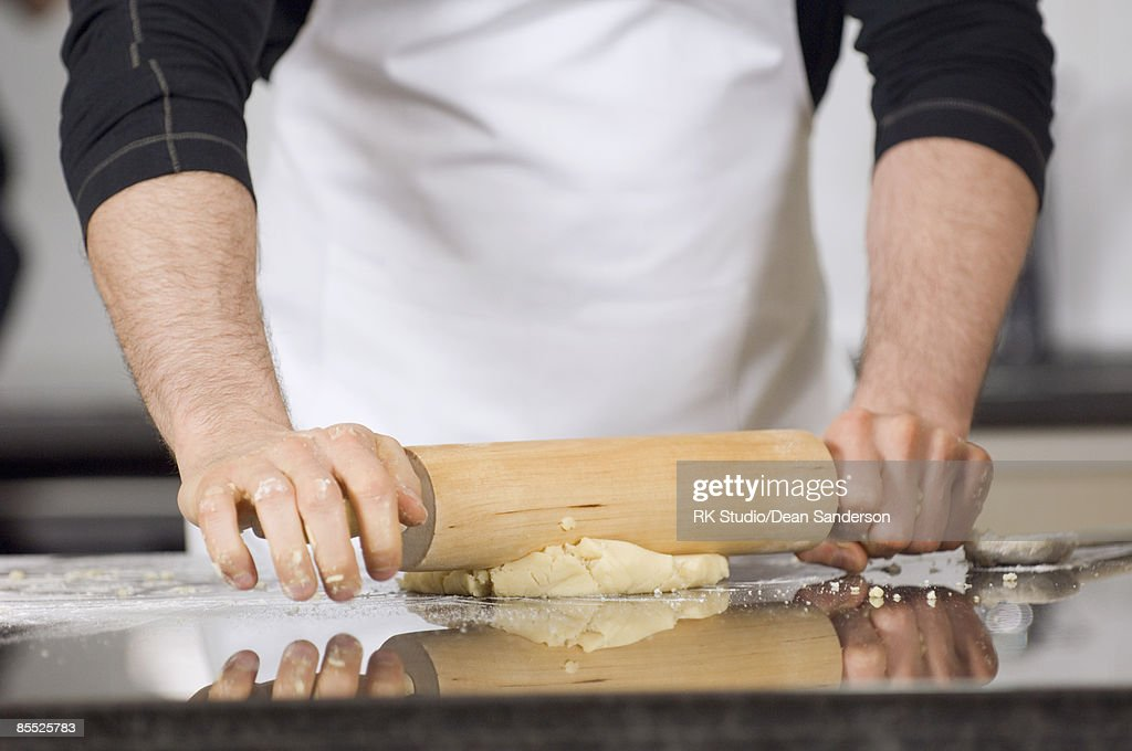 Close up of male hands rolling out dough.  : Stock Photo