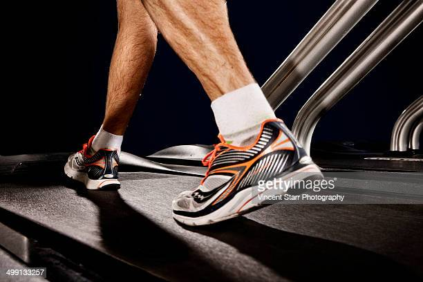 Close up of male legs running on gym treadmill in altitude centre