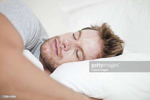 Close up of man asleep in bed