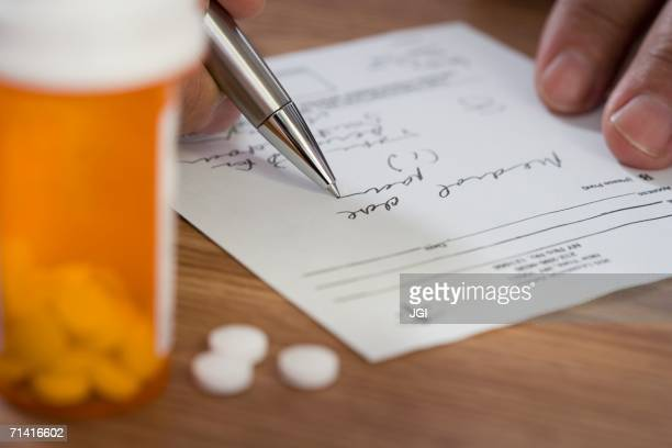 Close up of man filling out prescription